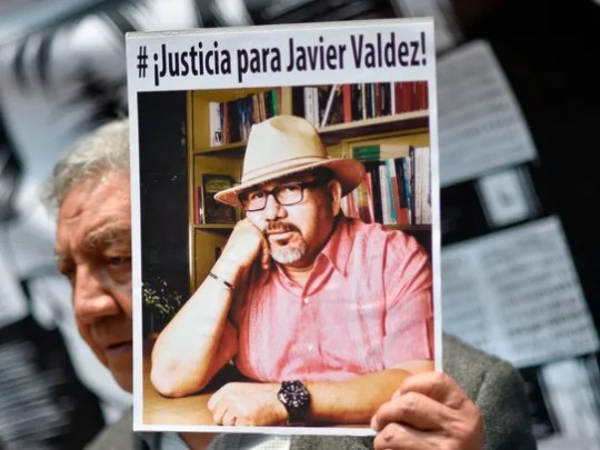 A journalist shows a picture of Mexican journalist