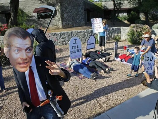 Chris Fleischman wears a mask as he protests near the
