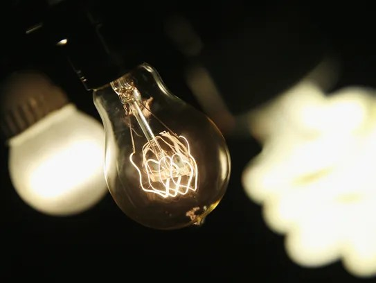 A vintage-style incandescent light bulb, center, is