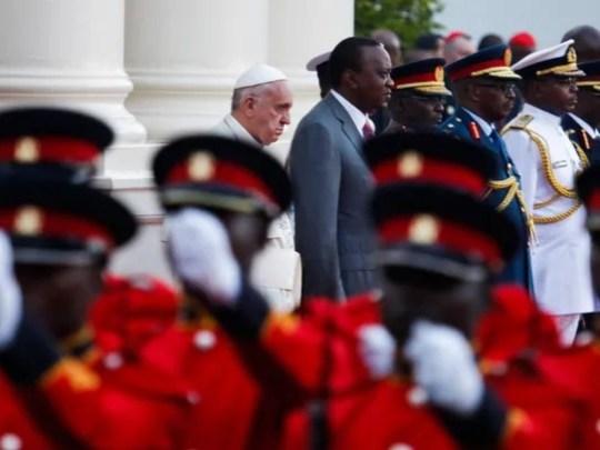 Pope Francis stands next to President Uhuru Kenyatta,