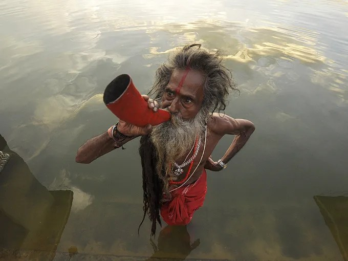 "An Indian ""sadhu,"" or  ""holy man,"" blows a buffalo horn on the eve of the traditional Kharchi Puja festival at Agartala.  Kharchi Puja is a week-long festival during which 14 gods are worshiped."