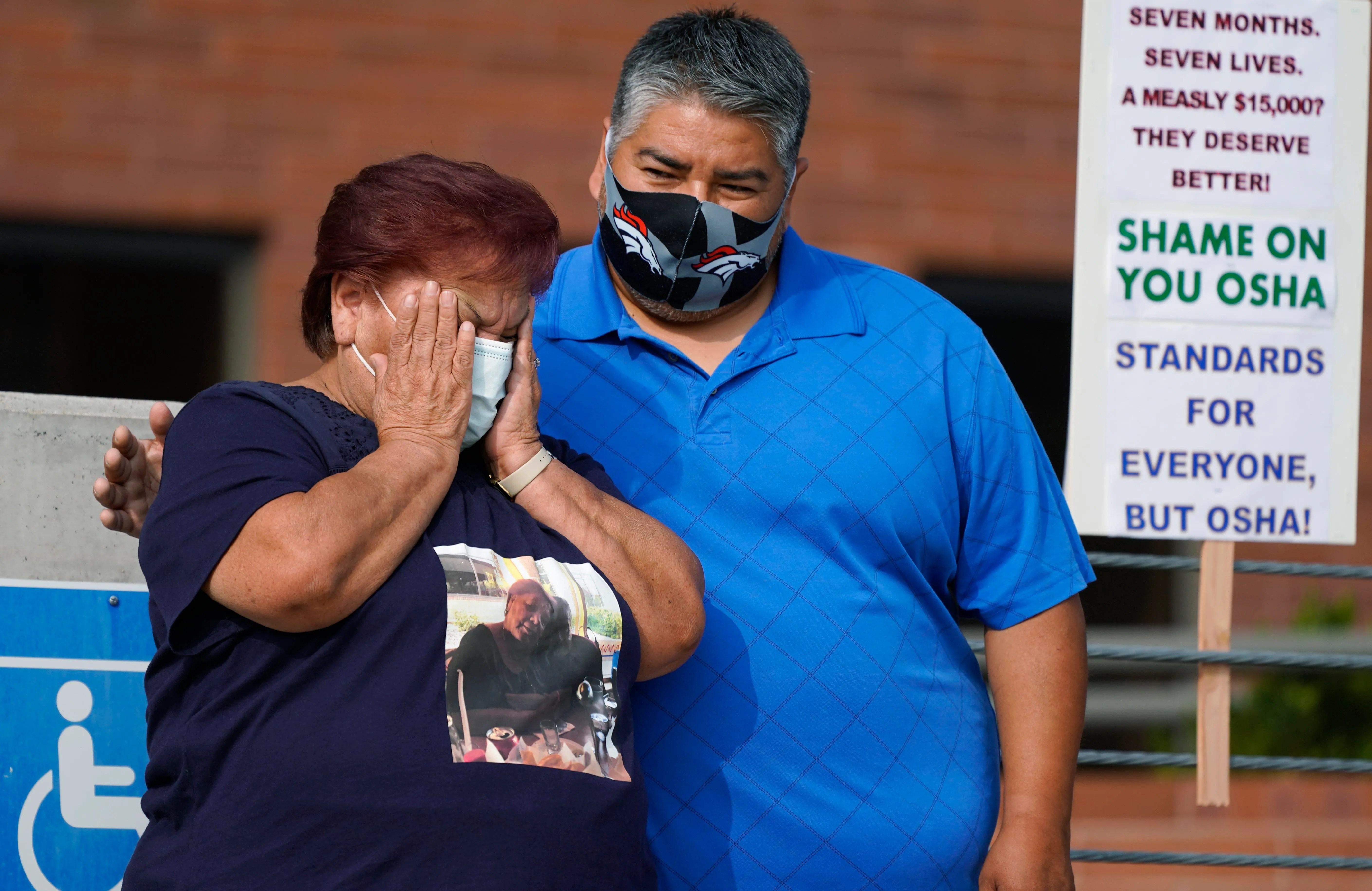 Widow Carolina Sanchez is comforted by her son, Saul, both of Greeley, Colo., during a protest staged by the union representing employees at a meatpacking plant where six workers died of COVID-19 and hundreds more were infected this past spring, outside OSHA offices in downtown Denver on Wednesday. Carolina Sanchez's husband was the first worker to die of COVID at the JBS Foods plant in Greeley.