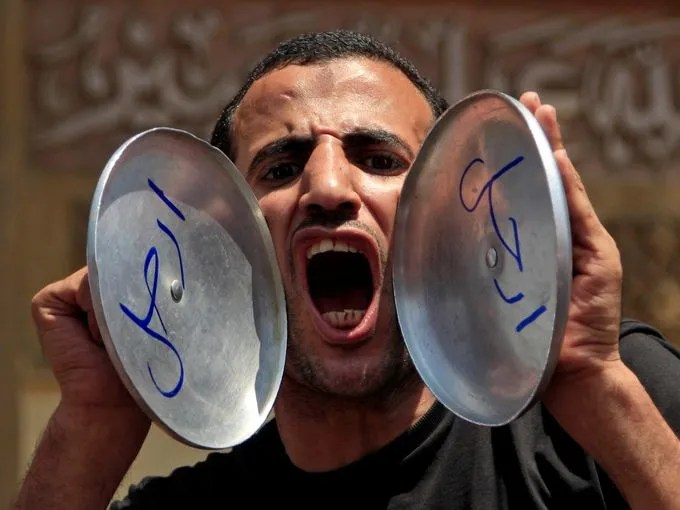 "An opponent of Morsi chants slogans as he holds pot covers with Arabic that reads, ""Leave."""