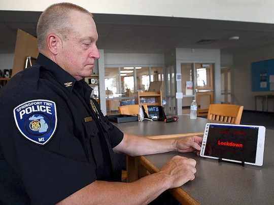 """Springport Twp. Chief of Police David Luce demonstrates the phone app that helps power the Springport, MI, Schools' new security system on Monday, Aug 20, 2018. The system uses a steel """"boot"""" placed in a slot at the bottom of the door, locking it to the floor."""