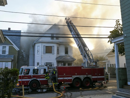 Firefighters battle a fire in a house in Lawrence, Mass.