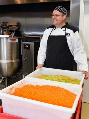 Chef Daniel Leavy gets ready to add a tub of chopped celery and onions and another tub of carrots to the 200-gallon kettle to make a healthy vegetable soup.