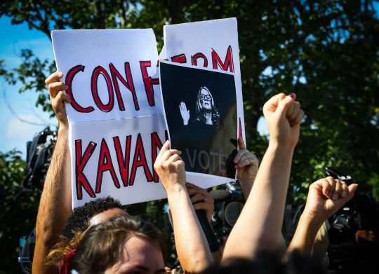 A supporter of Brett Kavanaugh is drowned out by people at a march in the nation's capital on Oct. 4, 2018.