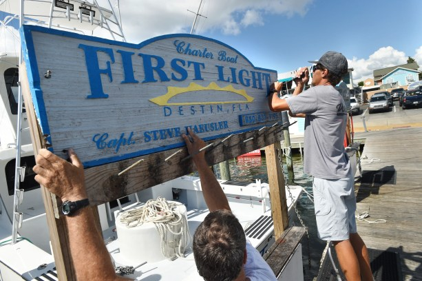 """O capitão Steve Haeusler, à esquerda, e Wyatt Ferreira pegaram a placa do barco de pesca """"First Light"""", de Haeusler, em 8 de outubro de 2018. Os capitães de barcos nesta comunidade pesqueira estão transportando seus navios para áreas mais seguras antes do furacão Michael."""