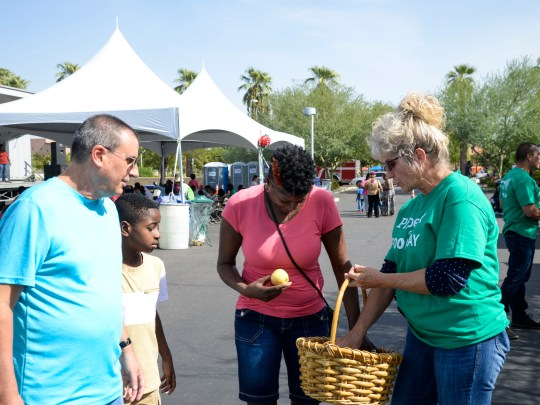A volunteer passes out free apples at Phoenix Food Day.