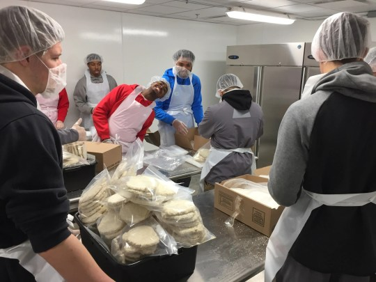 "Students from Central College break down packaged pork fritters into family-sized packages in the Food Bank of Iowa's newly added ""Clean Room."""
