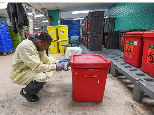 Charles Henry places a sticker on a hazardous material container. Henry said having a job makes him feel good about himself.