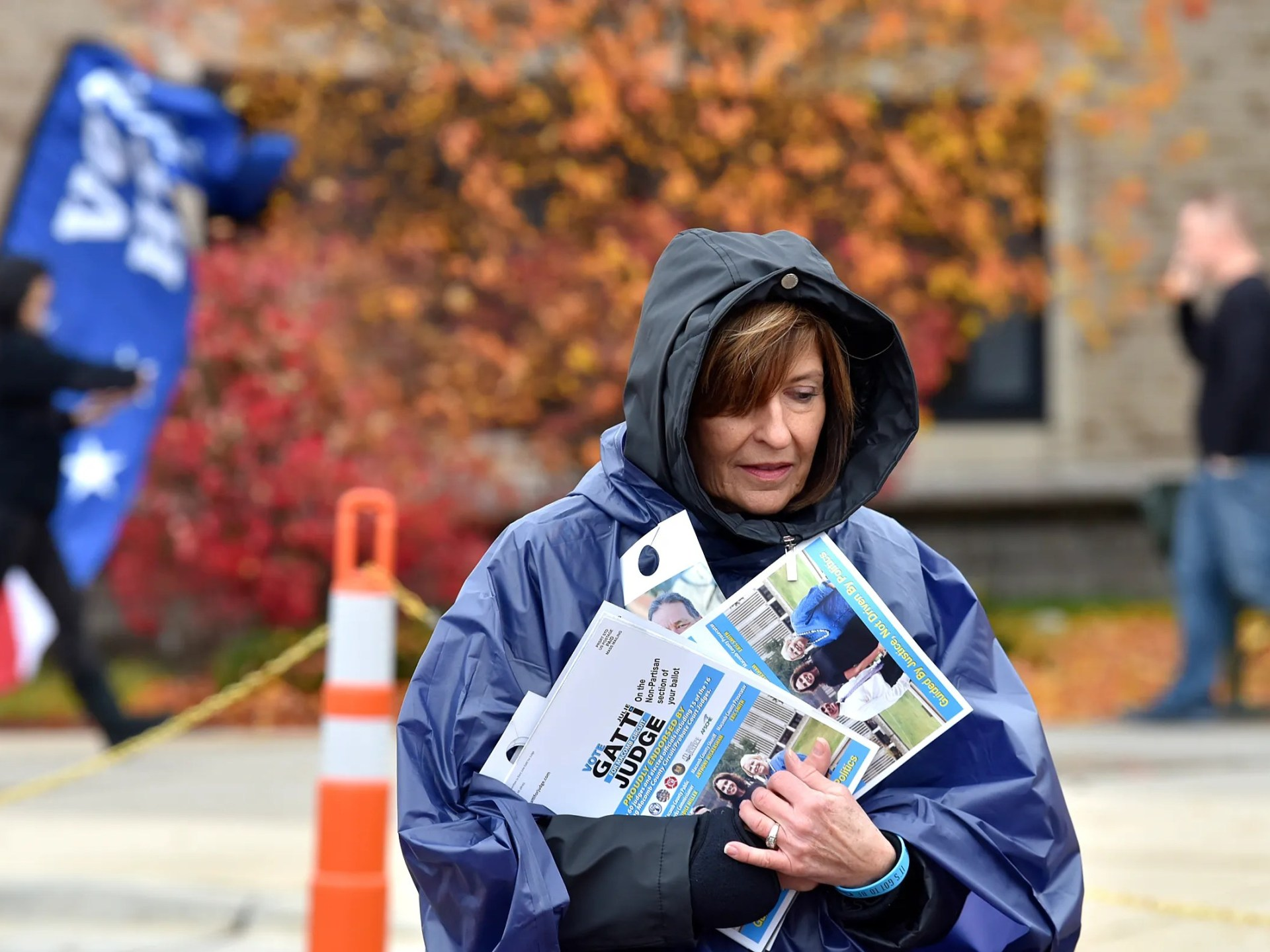 With blustery winds, rain and temperatures in the mid-50s, Linda Anderson of Macomb Township is bundled up to hand out campaign literature outside Ojibwa Elementary School. She is a volunteer for Julie Gatti, a candidate for Macomb County Circuit Court Judge.