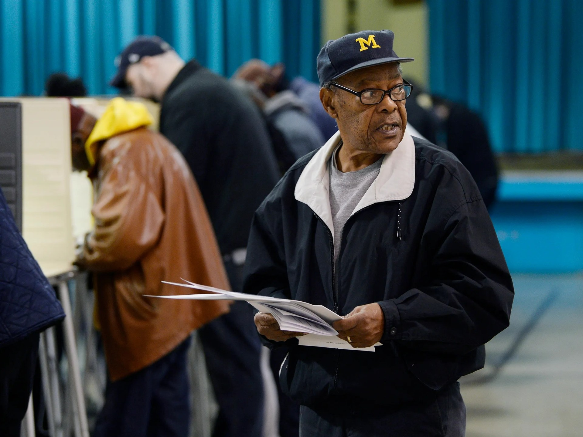 Floyd Hill, 77, of Southfield looks for the scanner to insert his ballot after voting at Adler Elemetary School in Southfield.