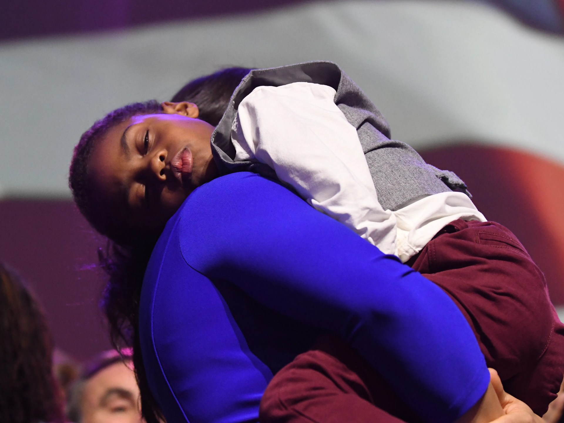 Lt. Governor-elect Garlin Gilchrist II's son falls asleep on his wife's shoulder at the  Democratic Party's election night event.