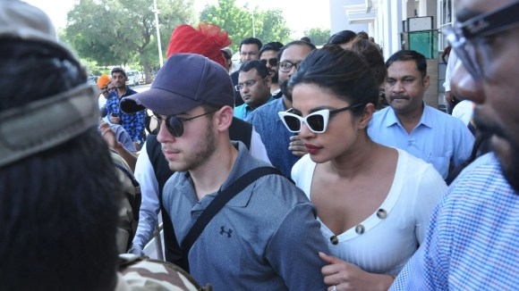 Priyanka Chopra and Nick Jonas walk out from the airport upon arriving in Jodhpur, in the Indian state of Rajasthan.