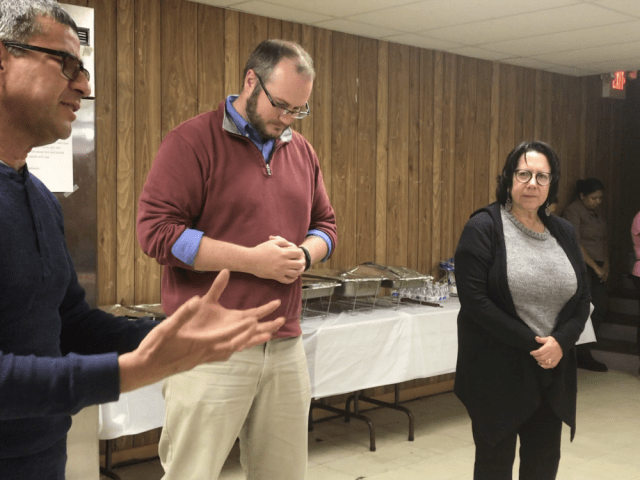 Rabbi Ellie Shemtov and Pastor Jonathan Elsensohn,right, listen along as Pastor Alejandro Junco, left, delivers a prayer at the inaugural Latino Supper Club, held Oct. 27 at the First Baptist Church of Freehold