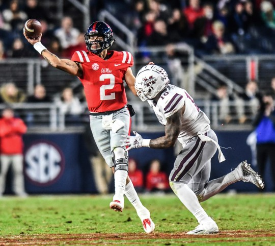 Mississippi quarterback Matt Corral (2) throws while being chased by Mississippi State linebacker Leo Lewis (10) during an NCAA college football game in Oxford, Miss., Thursday, Nov. 22, 2018.