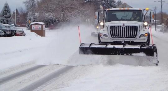 A snowplow fights flurries to keep roads open.
