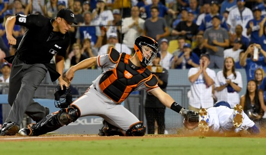 Giants catcher Buster Posey tags out Dodgers second baseman Brian Dozer during a game at Dodger Stadium.