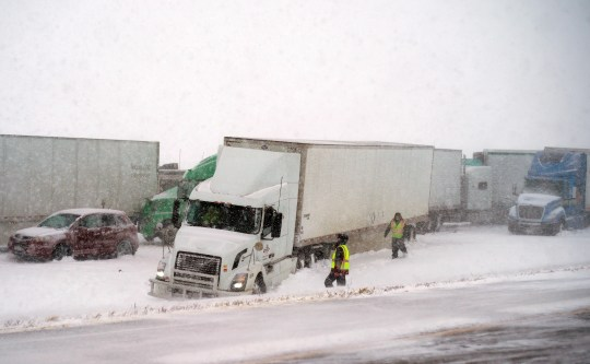 First responders check on drivers following a multi-vehicle crash on westbound Interstate 80 between Lincoln and Omaha, Neb., Saturday, Feb. 23, 2019. Blizzard conditions in south-central to southeastern Nebraska have led to several crashes and prompted officials to close a 120-mile stretch of Interstate 80 in the state.