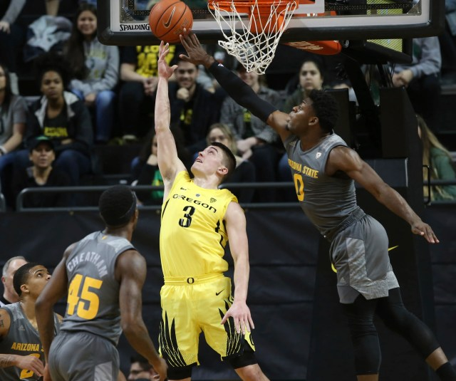 Oregon's Payton Pritchard, center, goes up for a reverse layup between Arizona State's Rob Edwards, left, Zylan Cheatham, and Luguentz Dort, right, during the first half of an NCAA college basketball game Thursday, Feb. 28, 2019, in Eugene, Ore.