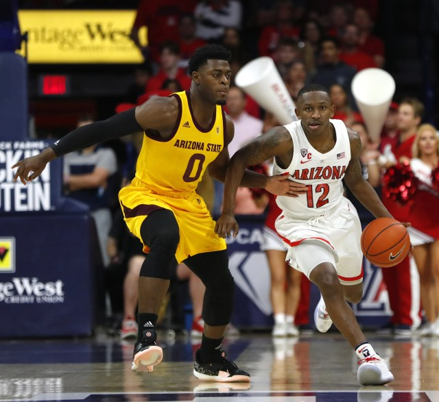 Arizona's Justin Coleman (12) dribbles against ASU's Luguentz Dort (0) during the first half at the McKale Memorial Center in Tucson, Ariz. on March 9, 2019.