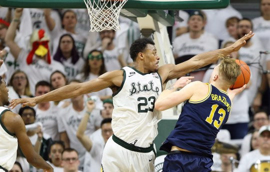 March 9, 2019; East Lansing, MI, USA; Michigan State Spartans puts forward Xavier Tillman (23) who puts Michigan Wolverines Ignas Brazdeikis (13) on hold during the second half of a game at Breslin Center.