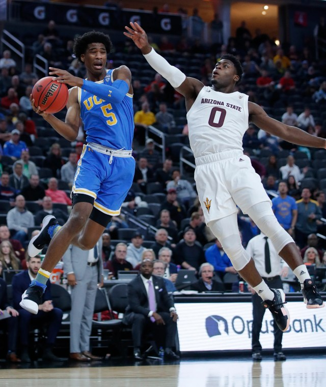 UCLA's Chris Smith, left, passes around Arizona State's Luguentz Dort during the first half of an NCAA college basketball game in the quarterfinals of the Pac-12 men's tournament Thursday, March 14, 2019, in Las Vegas.