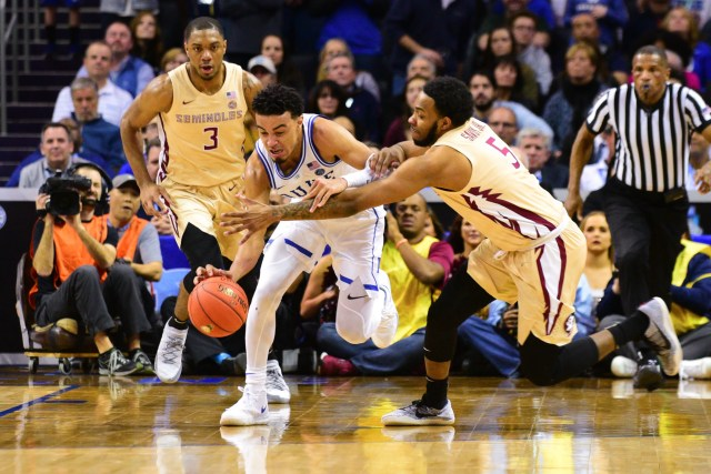 Florida State senior guard PJ Savoy, right, fouls Duke freshman guard Tre Jones, center, during the final minutes of the ACC Championship game at the Spectrum Center on Saturday.
