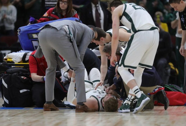 Michigan State players gather around Kyle Ahrens before he left the court with a foot injury against Michigan in the Big Ten tournament championship Sunday, March 17, 2019 in Chicago.