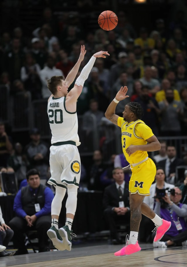 Michigan State's Matt McQuaid scores a 3-pointer over Michigan's Zavier Simpson during the first half of the Big Ten tournament championship Sunday, March 17, 2019 in Chicago.