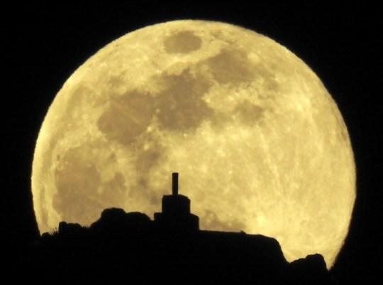 A view of the full moon over Mount Pico Sacro, just outside Santiago de Compostela, Spain.