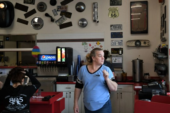 Byron Taylor's daughter-in-law Sally Windh seats guests and serves customers at The Corner Cafe. Taylor passed away on Saturday but the diner will continue to honor his memory.