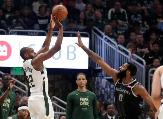 Bucks forward Khris Middleton launches and cans a three-pointer over Pistons center Andre Drummond during the first half.