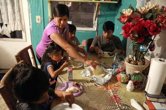 Bernabela Gonzalez serves freshly made tortillas for dinner in the trailer her family rents in Immokalee on Wednesday evening.