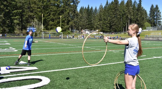 North Mason High School student Adam Moore, 15, throws a football through a hula hoop at the Day of Champions track and field event at North Mason High School on Thursday. At Day of Champions, students in grades kindergarten through 12th grade spend the day playing non-competitive modified sports