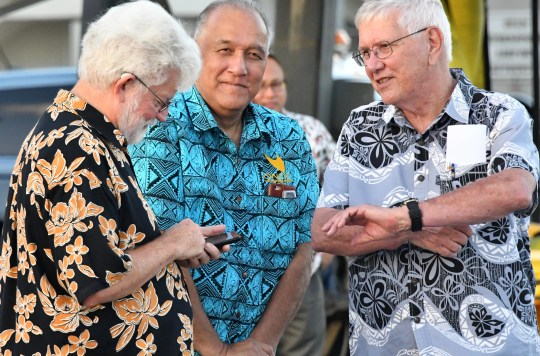 First gentleman Jeffrey Cook, left, along with Guam National Olympic Committee president Ricardo Blas, center and secretary general Bob Steffy, await the arrival of IOC president Thomas Bach on the tarmac of the AB Won Pat Guam International Airport on May 10, 2019.