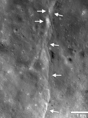A fault line (shown by the white arrows) on the lunar surface.