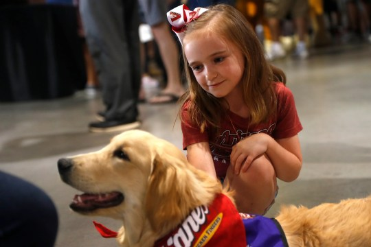 Haylie Birchamn, 6, Brenly's pet, a rescue dog being trained to become a therapy dog through Angels Gabriel, before Diamondbacks game at Chase Field in Phoenix Sunday.