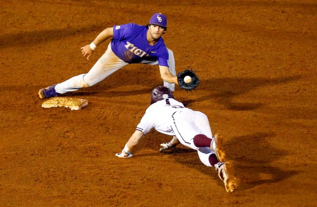LSU shortstop Josh Smith (4) catches the ball to tag Mississippi State's Tanner Allen (5) out as he slides into second base during the 15th inning of the Southeastern Conference tournament NCAA college baseball game, Thursday, May 23, 2019, in Hoover, Ala. (AP Photo/Butch Dill)