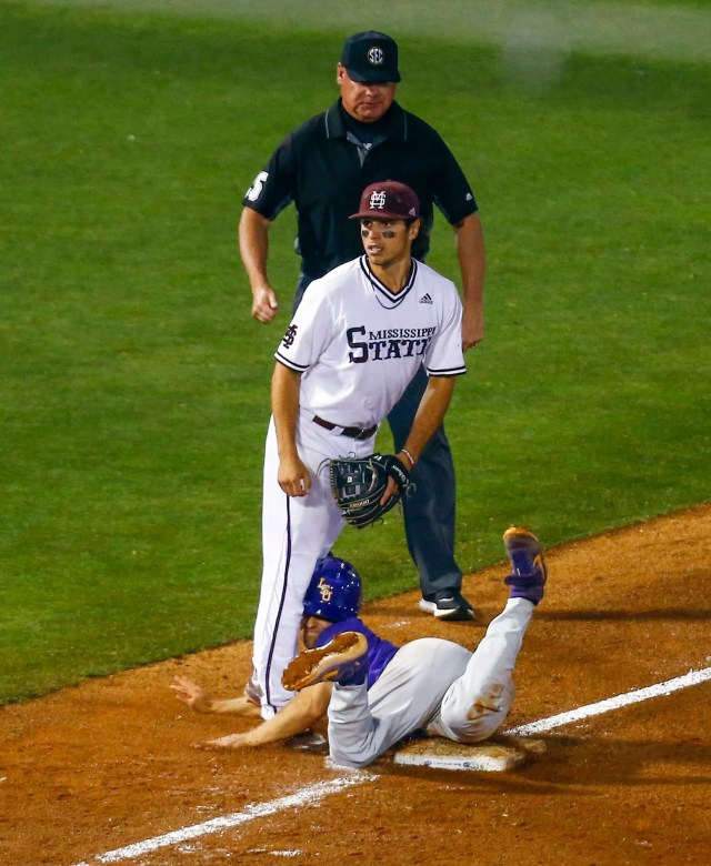 LSU's Josh Smith collides against the legs of Mississippi State third baseman Marshall Gilbert as he slides safely past the bag during the fifth inning of a Southeastern Conference tournament NCAA college baseball game Wednesday, May 22, 2019, in Hoover, Ala. (AP Photo/Butch Dill)