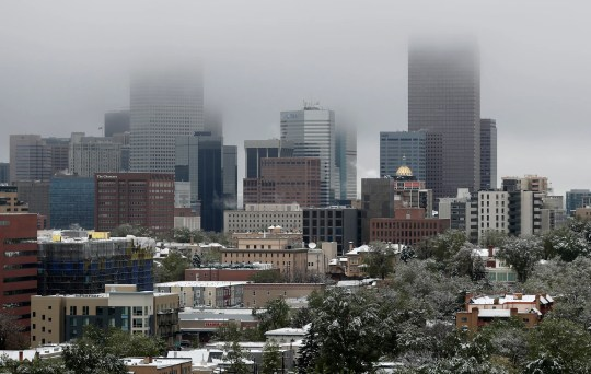 Low clouds hang through the tops of the skyscrapers as a spring storm sweeps over the metropolitan area Tuesday, May 21, 2019, in Denver, Colorado. The spring snowstorm that swept over the region Monday night into Tuesday dropped three to six inches of snow in the metropolitan area but up to a foot or more in the mountains.