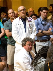 In this July 23, 2013, photo provided by Jenny Warburg, Dr. Charles van der Horst, standing at center, joins a Moral Monday protest at the state legislative building in Raleigh, N.C. He went missing during a marathon swimming race down New York's Hudson River on Friday and was declared dead by his family Saturday. Tim Tyson sits before Van der Horst.