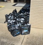 More than a dozen Patrol Packs sit on the sidewalk in front of the Baxter County Sheriff's Office on Thursday. AT&T is providing the food kits to the Sheriff's Office for deputies to hand out while on patrol.