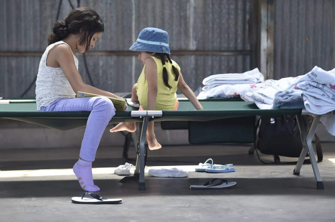 Two migrant children sit and read on a cot in the Deming migrant shelter, Friday, June 28, 2019, in Deming, New Mexico.