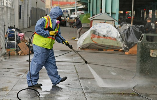 A street cleaner in San Francisco power washes the sidewalk in this 2016 file photo. The city's homelessness issue, driven in part by a lack of affordable housing, has become a major problem for lawmakers and residents alike, prompting some to flee the tech hub.