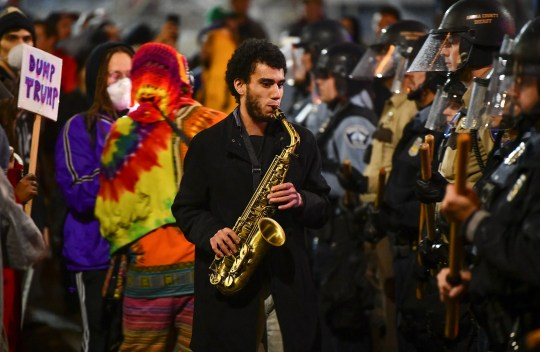 Matthew Trice plays the saxophone between protesters and a police line following the rally for Donald J. Trump Thursday, Oct. 10, 2019, outside the Target Center in Minneapolis.