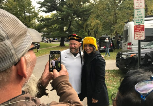 """Brian Decouster and U.S. Rep. Tulsi Gabbard pose for a photo in Iowa City after he gave the 2020 Democratic presidential candidate a Russian cossack hat as a joke referencing recent allegations that she is a """"Russian asset."""""""