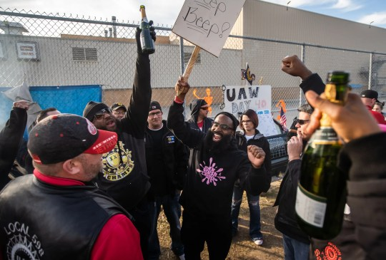UAW Local 598 Alternate Committee rep Will McIntosh (center left) and Alternate Committee rep Stanley Dulaney throw their hands in the air while celebrating outside of Flint Assembly after UAW ratified their contract with General Motors marking the end of the strike on Friday, October 25, 2019.