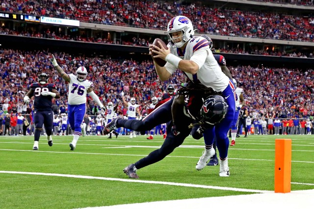Buffalo Bills quarterback Josh Allen (17) scores a touchdown against Houston Texans strong safety Jahleel Addae (37) during the first quarter in the AFC wild-card playoff game at NRG Stadium.